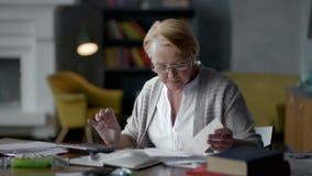 Starsza kobieta martwi się o rachunkach rozumie że wszystko jest dobrze uspokaja puszek, oddycha wolno, zbiory