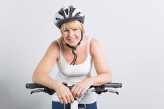Starsza kobieta na stronie rower w pracownianym białym tle zdjęcie royalty free