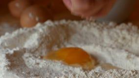 Starsza kobieta nalewa jajko na mące zbiory