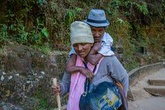 Starsza kobieta niesie jej niepełnosprawnego męża na ona z powrotem Fotografia Royalty Free