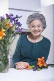 Starsza kobieta Obok bukieta kwiaty w kuchni, portret Obrazy Stock