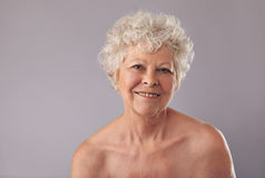 Starsza kobieta ono uśmiecha się na popielatym tle Obraz Royalty Free