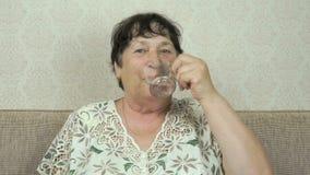 Starsza kobieta ono uśmiecha się, napoje nawadnia up, przedstawienie kciuk zdjęcie wideo
