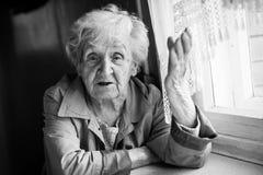 Starsza kobieta opowiada i gestykuluje podczas gdy siedzący przy stołem grandmaster fotografia royalty free