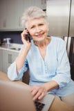 Starsza kobieta opowiada na telefonie i używa laptop Fotografia Stock