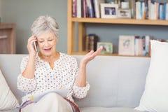 Starsza kobieta opowiada na telefonie komórkowym podczas gdy patrzejący dokument zdjęcia stock