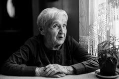 Starsza kobieta opowiada siedzieć przy stołem w domu Obraz Royalty Free