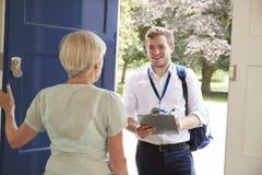 Starsza kobieta otwiera drzwi męski dobroczynność pracownik robi ankiecie zdjęcia royalty free