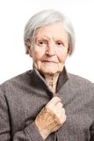 Starsza kobieta patrzeje kamerę nad bielem Obraz Royalty Free