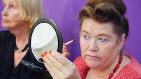 Starsza kobieta patrzeje odzwierciedlać i stosuje makeup z kosmetyka muśnięciem zbiory wideo