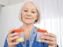 Starsza kobieta Patrzeje pigułek butelki fotografia royalty free