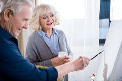 Starsza kobieta patrzeje sztalugę podczas gdy uśmiechnięty mężczyzna obrazu obrazek Obraz Stock