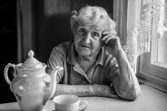 Starsza kobieta pije herbaty przy stołem Zdjęcia Stock