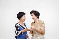 Starsza kobieta pije herbaty z jej córką bierze opiekę, odosobnioną obraz royalty free