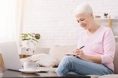 Starsza kobieta pisze puszka dzia?aniu i my?lach na laptopie zdjęcie royalty free