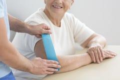 Starsza kobieta podczas kinesiotaping obrazy stock