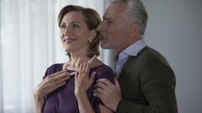 Starsza kobieta podziwia perełkową kolię, mężczyzna przytulenie od behind, całowanie jej policzek zdjęcie wideo