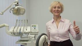 Starsza kobieta pokazuje jej kciuk up przy dentysty biurem zdjęcie wideo
