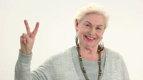 Starsza kobieta pokazuje pokoju gest zdjęcie wideo