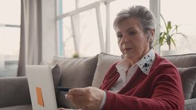 Starsza kobieta próbuje online pieniądze zapłatę laptopem i nową kartą kredytową zdjęcie wideo