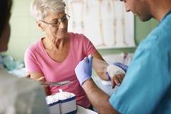 Starsza kobieta przy lekarki biurem Obraz Stock