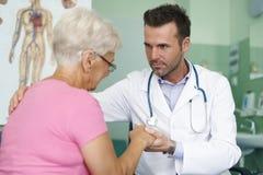 Starsza kobieta przy lekarki biurem Zdjęcie Royalty Free
