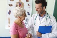 Starsza kobieta przy lekarki biurem Zdjęcie Stock