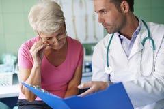 Starsza kobieta przy lekarki biurem Fotografia Stock