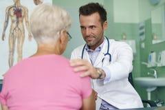 Starsza kobieta przy lekarki biurem Obrazy Stock