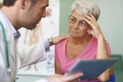Starsza kobieta przy lekarki biurem Zdjęcia Stock