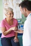 Starsza kobieta przy lekarki biurem Zdjęcia Royalty Free