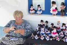 Starsza kobieta przy ulicą robi sprzedaje tradycyjne handmade lale Nazare, Portugalia obraz royalty free