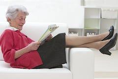 Starsza kobieta relaksuje w czytaniu Fotografia Royalty Free