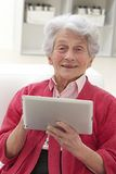 Starsza kobieta relaksuje z jej laptopem Zdjęcia Royalty Free