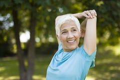 Starsza kobieta robi ćwiczeniu dla rozciągać rękę w parku zdjęcia royalty free