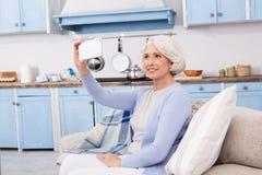 Starsza kobieta robi jaźni fotografiom obrazy royalty free