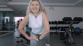 Starsza kobieta robi kucaniom w gym Starszej kobiety Starsza kobieta robi sporta ćwiczeniom w gym zdjęcia royalty free