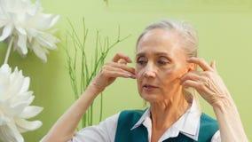 Starsza kobieta robi twarzowemu masażowi w domowej łazience Dojrzała kobiety masowania twarzy skóra na kosmetykach kursowych wewn zbiory