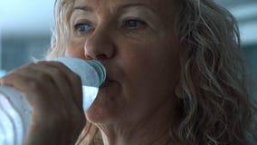Starsza kobieta słucha muzyka z hełmofonami i wodą pitną od butelki na karuzeli w gym, zakończenie w górę obraz stock