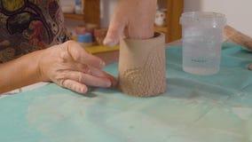 Starsza kobieta sculpting glinianego kubek zbiory