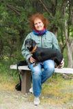 Starsza kobieta siedzi na ławce w jałowcowym gaju z jamnikiem Fotografia Stock