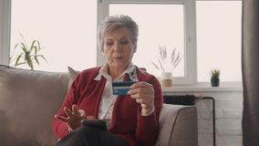 Starsza kobieta siedzi na trenerze i robi zakupy online używać dla płatniczego karty kredytowej i technologii cyfrowej smartphone zbiory