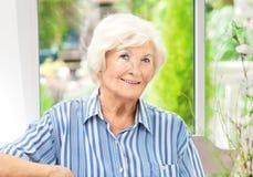 Starsza kobieta siedzi w domu obraz royalty free