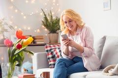 Starsza kobieta siedzi w domu wyszukujący smartphone radosnego zdjęcie stock