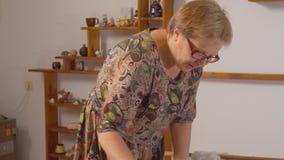 Starsza kobieta stacza się glinę jak ciasto zdjęcie wideo
