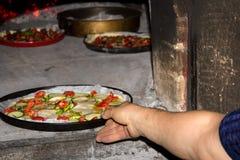 Starsza kobieta stawia pizzę w tradycyjnego Włoskiego piekarnika obrazy royalty free