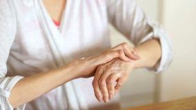 Starsza kobieta stosuje nawilżanie płukanki śmietankę na ręki palmie, łagodzi boli Starszy starej damy doświadczać surowy zbiory