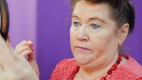 Starsza kobieta stosuje oka makeup na twarz przodu lustrze zamkniętym w górę trochę zdjęcie wideo