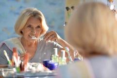 Starsza kobieta szczotkuje jej zęby Fotografia Stock