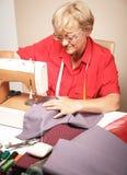 Starsza kobieta szy na szwalnej maszynie zdjęcia royalty free